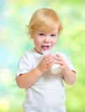 Barn som dricker mejeriprodukten från exponeringsglas arkivfoton