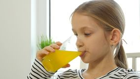 Barn som dricker orange fruktsaft, unge p? frukosten i k?k, ny flickacitron arkivfilmer