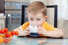 Barn som dricker yoghurt eller kefir Arkivbilder