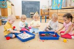 Barn som förbättrar motorisk expertis för händer med ris och bönor Royaltyfria Bilder