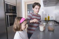 Barn som förbereder ett exponeringsglas av, mjölkar Arkivbild