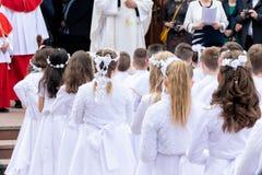Barn som förbereds för den första nattvardsgången, väntar framme av kyrkan royaltyfri bild