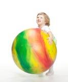 Barn som försöker att bära enorm fitball Arkivbild