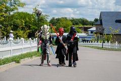 Barn som förställas i Star Wars dräkter: Pilstor trähammare, Darth Vader med svärd royaltyfria foton