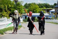 Barn som förställas i Star Wars dräkter: Pilstor trähammare, Darth Vader med svärd Darth Vader arkivfoto