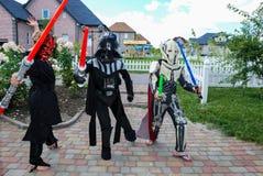 Barn som förställas i Star Wars dräkter: Pilstor trähammare, Darth Vader med svärd Darth Vader arkivbilder