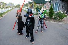 Barn som förställas i Star Wars dräkter: Pilstor trähammare, Darth Vader med svärd Darth Vader royaltyfri foto