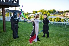 Barn som förställas i Star Wars dräkter: Pilstor trähammare, Darth Vader med svärd arkivfoton