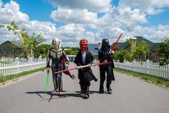 Barn som förställas i Star Wars dräkter: Pilstor trähammare, Darth Vader med svärd Darth Vader, royaltyfri fotografi