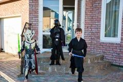 Barn som förställas i Star Wars dräkter: Pilstor trähammare, Darth Vader med svärd Darth Vader, royaltyfria foton
