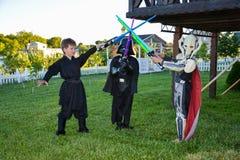 Barn som förställas i Star Wars dräkter: Pilstor trähammare, Darth Vader med svärd Darth Vader arkivfoton