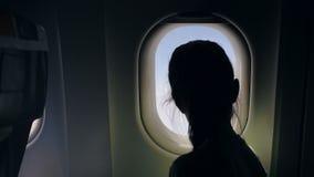 Barn som förutom ser flygplanfönstret arkivfilmer