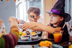Barn som firar allhelgonaafton på dagiset som äter tematiska sötsaker royaltyfri bild