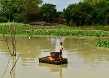 Barn som fiskar på en flod i Cambodja arkivfoton