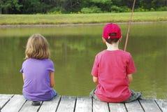 Barn som fiskar på skeppsdocka royaltyfria foton