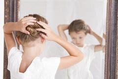 Barn som fixar hennes hår, medan se i spegeln arkivfoton