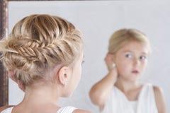 Barn som fixar hennes hår, medan se i spegeln fotografering för bildbyråer