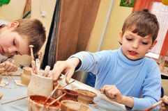 Barn som formar lera i krukmakeristudio Arkivbild