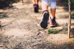 Barn som fotvandrar i berg eller skog med sporten som fotvandrar skor Arkivfoto