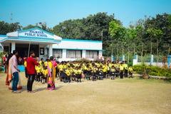Barn som framme ber nationalsången för skolastarter i likformig av skolabyggnad med lärarna arkivbild
