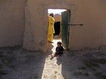 Barn som framme står av en dörr i Afghanistan Royaltyfria Bilder