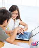 Barn som fungerar på deras bärbar dator 免版税库存图片