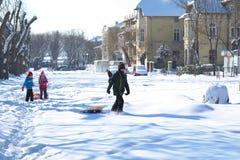Barn som går i gatan, kröp ihop med snö Fotografering för Bildbyråer
