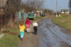 Barn som går i ukrainsk by Arkivbild