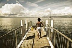 Barn som går längs en liten brygga i laken Leman Arkivfoton