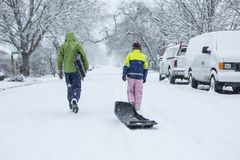 Barn som går till och med en snöig grannskap med en släde Arkivbild