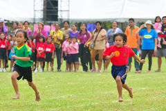Barn som gör en teamwork, kör att springa på dagissportdagen Arkivbild