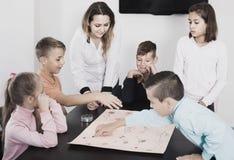 Barn som gör flyttning på pre-markerad yttersida av brädeleken arkivfoton