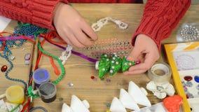Barn som gör garnering för ferier, hantverk och leksaker, julträd och annat Målningvattenfärger Top beskådar Konstverkworkpl stock video