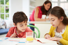 Barn som gör läxa som moder, använder bärbara datorn Arkivfoton