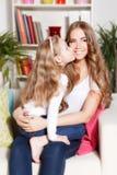Barn som ger en kyss till modern Royaltyfri Foto