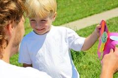 Barn som ger fader en gåva Arkivfoto