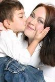 barn som ger kyssmodern royaltyfri foto