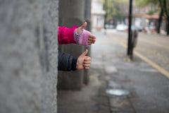 Barn som ger upp tummar Arkivfoto