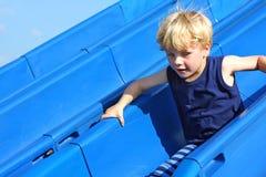 Barn som glider på lekplatsen Arkivfoto