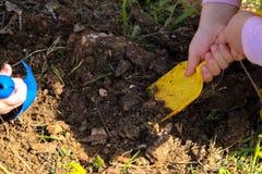 Barn som gräver i jordningen med en skyffel Tu B 'Shvat i Israel royaltyfri foto