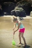 Barn som gräver i sanden med en skyffel Arkivfoton