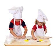 Barn som gör kakor som kläs som kockar Arkivbilder