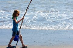 Barn som går på stranden med en stick Arkivfoton