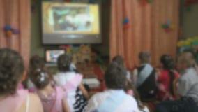 Barn som håller ögonen på bilderna genom att använda en projektor arkivfilmer