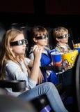Barn som håller ögonen på filmen 3D i teater Fotografering för Bildbyråer