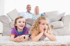 Barn som håller ögonen på TV medan föräldrar som sitter på soffan Royaltyfria Bilder