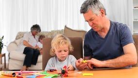 Barn som har differentsaktiviteter med deras morföräldrar stock video
