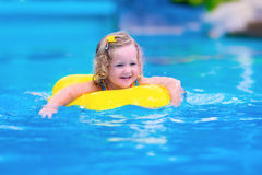 Barn som har gyckel i en simbassäng Arkivfoto