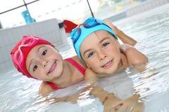 Barn som har gyckel i simbassäng royaltyfri fotografi