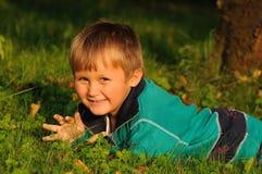 Barn som har gyckel i trädgård Arkivfoton